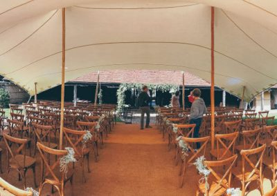 A Wedding ceremony under a white stretch tent with our wooden folding chairs