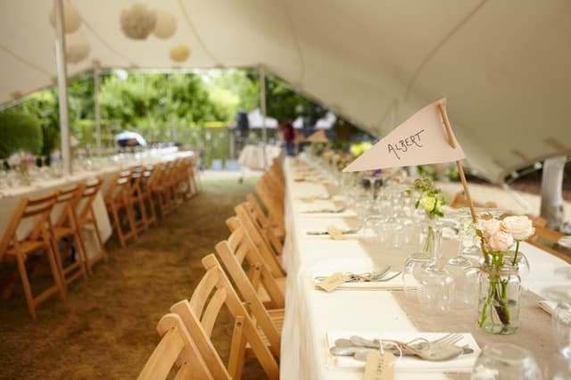 Summer wedding table layouts under a white stretch tent