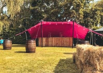 pink tent with whiskey barrels and bar